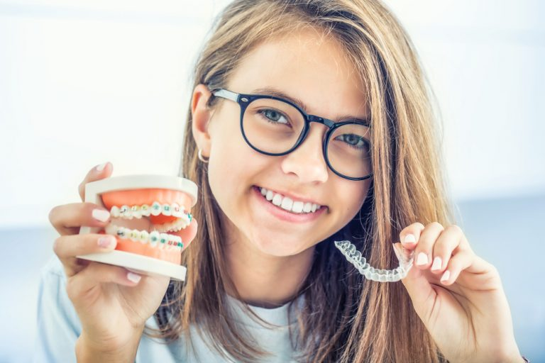 girl holding invisalign and braces
