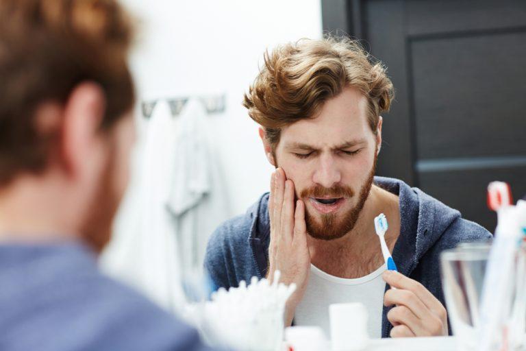 Man With Sensitive Teeth Touching His Cheek