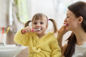 child and parent brushing teeth
