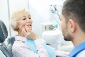 woman in dental chair in pain